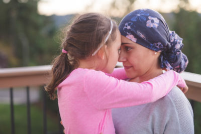 A young mother fighting cancer and wearing a head scarf hugs her daughter. They have their arms around each other and they are touching noses and looking into each other's eyes. They are outside on a deck.Dieser Artikel ist erschienen inDer Hausarzt 18/2018Seite 8DownloadPDF-Dokument1 Seite(n)Größe: 169,22 kB