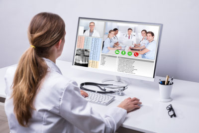 Rear View Of A Female Doctor Video Conferencing With Colleagues On Computer In Clinic