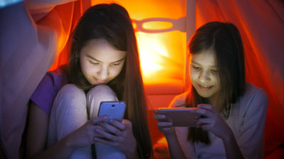 Portrait of two sisters in pajamas using smartphones under blanket at night
