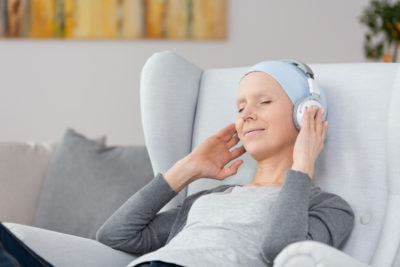 Woman with cancer listening to music on headphones at home