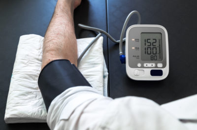 man self-monitoring of blood pressure with a tensiometer / Hypertensive patient performing a blood pressure auto test