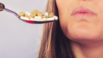 Closeup of woman patient not taking pills. Girl female and stack of tablets. Health care concept.