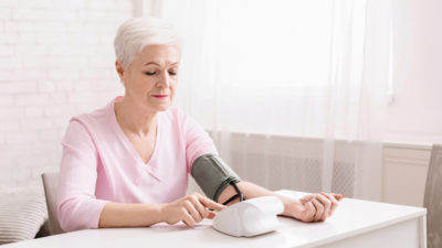Senior woman measuring her blood pressure at home, free space