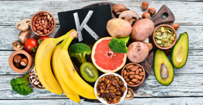Foods containing natural potassium. K: Potatoes, mushrooms, banana, tomatoes, nuts, beans, broccoli, avocados. Top view. On a white wooden background.