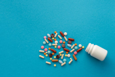 A handful of colored pills spilled out of the can on a blue background. Medical concept.