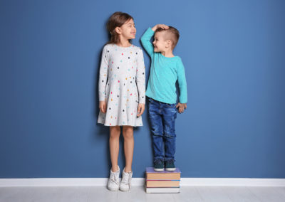 Little girl and boy measuring their height near color wall