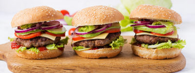 Big sandwich - hamburger burger with beef, avocado, tomato and red onions on light background. American cuisine. Banner. Fast Food