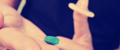 closeup of a young man with a blue pill in one hand and a condom in the other hand, with a filter effect