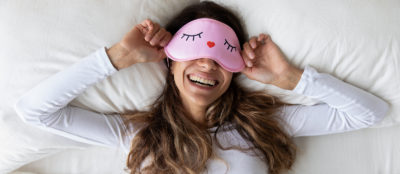 Above top view head shot happy millennial mixed race healthy woman lying in bed with sleeping mask, waking up after sweet dreams. Smiling young relaxed lady feeling energetic in morning at home.