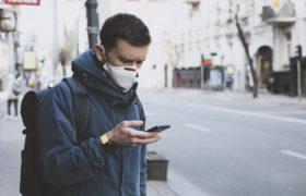 Mann mit Maske und Handy