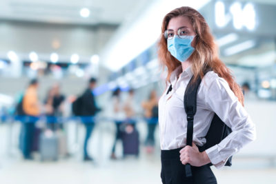 Virus mask woman travel wearing face protection in prevention for coronavirus at airport. Lady walking in public space check in counter airport.Coronavirus or covid 19 concept