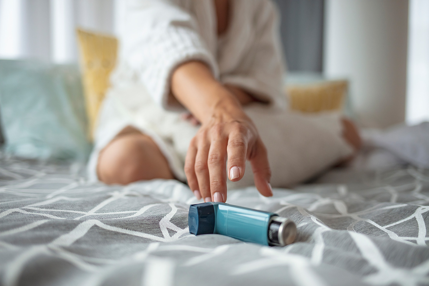 Girl suffering asthma attack reaching inhaler sitting on a bed in the bedroom at home. Woman Hand Reaching Inhaler Because She Suffering From Asthma Attack