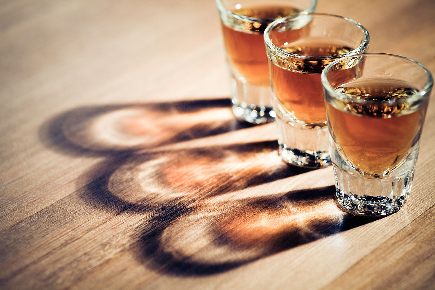 three shot glasses full of dark colored alcohol on top of a bar table. The shot could be whiskey, dark rum, tequila, cognac, or bourbon.